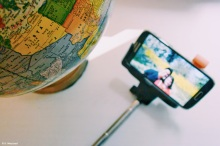 Globe and selfie stick on white surface